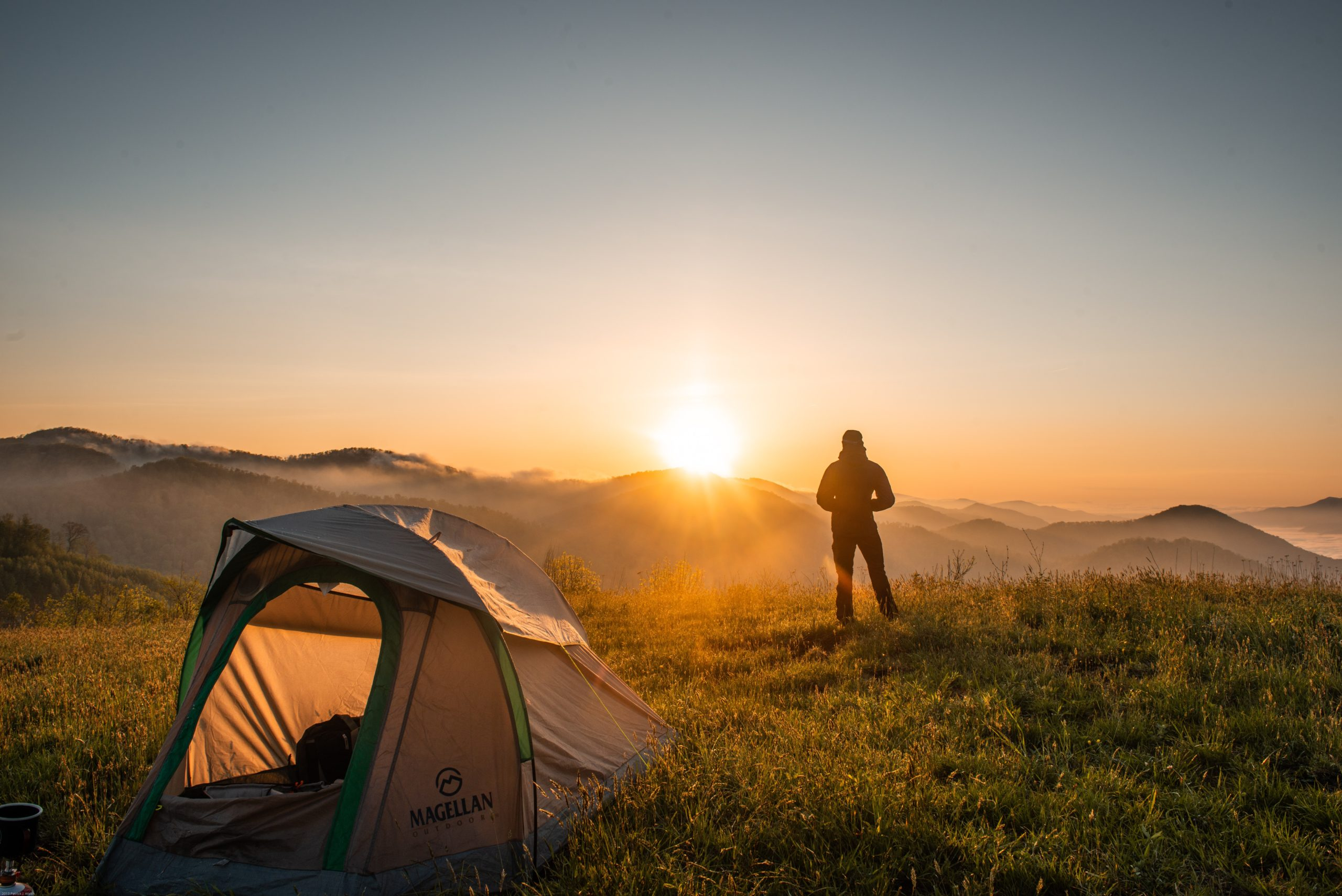 A man standing infront of his tent